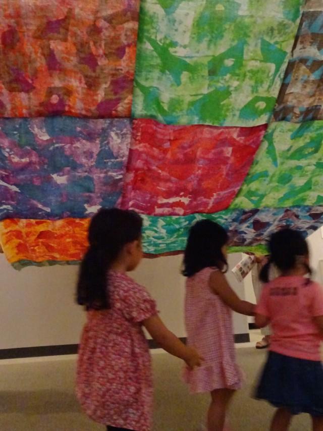 染色家によって染められ繋がれた巨大な布の下を通る子どもたち